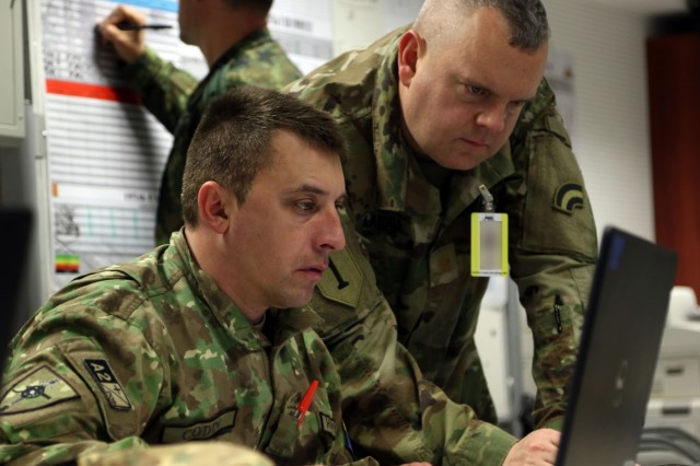U.S. Army Soldier (right), an assistant chief of operations with the 42nd  Infantry Division observes a training plan with Master Sgt. Cosmin Codin, a Romanian soldier, during exercise Dynamic Front 19, March 4 at Grafenwoehr Training Area, Germany. Dynamic Front 19 is a multinational exercise conducted by the U.S. Army in Europe designed to improve allied and partner nation ability to deliver long-range fire capabilities. It allows Allies to connect personally, professionally, technically and tactically to create stronger and more capable forces in time of crisis. (U.S. Army photo by Sgt. John Onuoha / Released)