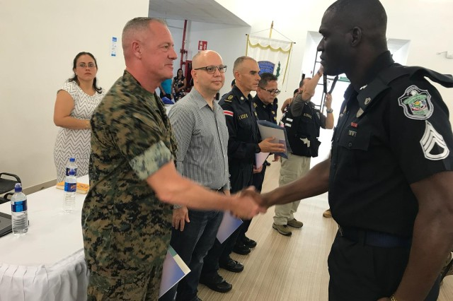 (from left to right) SGM Bryan K. Zickefoose , SOUTHCOM Command Senior Enlisted Leader, presents a seminar certificate to Sgt. Humphreys, Panamanian National Police member. Also present were, Mr. Michael Soto, Costa Rican Minister of Public Security, Comisario (COL) Eric Lacayo Rojas, Director, Costa Rican Police Academy, Comisario (COL) Walter Navarro, WHINSEC Sub Commandant for Police Affairs