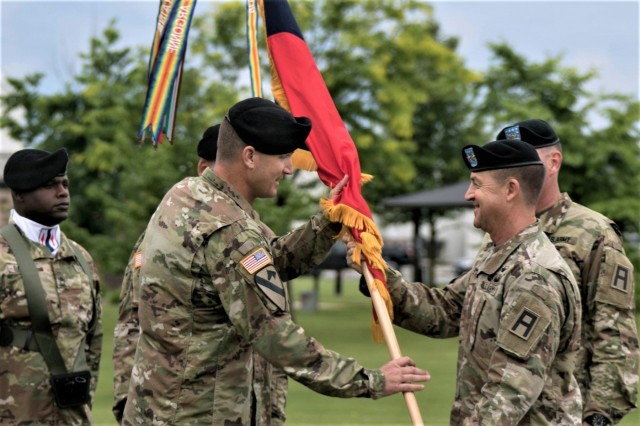 Col. David C. Woodruff Jr. takes the 181st Multi-Functional Training Brigade flag from Maj. Gen. Erik C. Peterson, commanding general of First Army Division West at Fort Hood, Texas, in assuming command of the brigade during a change of command ceremony June 28, 2019, at Fort McCoy, Wis. Peterson was the presiding officer for the ceremony. The 181st MFTB, a tenant organization at Fort McCoy, partners with Army Reserve and Army National Guard units to advise, assist, and train Army formations throughout their complete sustainable readiness model cycle to achieve collective training readiness in support of worldwide requirements. (U.S. Army Photo by Staff Sgt. Robert Larson, 181st Multi-Functional Training Brigade)