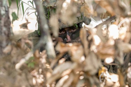 University of Missouri cadet takes cover in the brush to hide himself and his weapon from the enemy. Field training exercises cultivate leadership skills in cadets for Cadet Summer Training at Fort Knox, Ky., July 9, 2019.