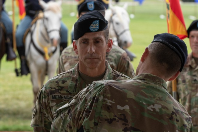 Brig. Gen. Joseph Ryan, acting senior commander, 4th Infantry Division and Fort Carson, presents Col. Norberto Menéndez, outgoing commander, 4th Division Artillery, with a Legion of Merit prior to the change-of-command ceremony at Founders Field, Fort Carson, Colorado, June 13, 2019. The ceremony represents the passing of command from Col. Norberto Menéndez to Col. Ryan Maender.  (U.S. Army photo by Spc. Robert Vicens)