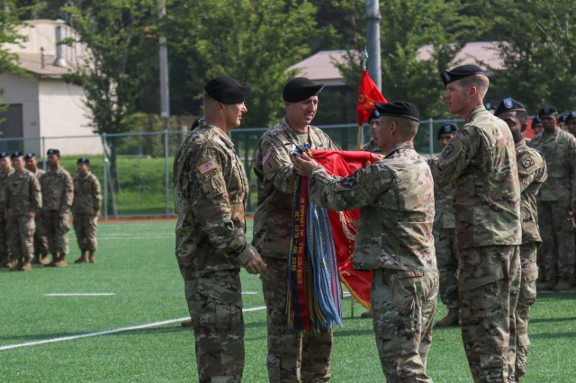 Major Gen. Steve Gilland, 2nd Infantry Division/ROK-US Combined Division commanding general, left, and Command Sgt. Maj. Phil Keli'i Barretto, Hawaii native, 2ID/RUCD command sergeant major, front right, affix a streamer to 3rd Battalion, 13th Field Artillery Regiment's (rotational) colors, 210th Field Artillery Brigade, in recognition of their successful nine-month rotation to the Republic of Korea, July 19, 2019, Camp Casey, Republic of Korea. The 2-18 FAR is a multiple launch rocket system battalion assigned to 75th Field Artillery Brigade out of Fort Sill, Oklahoma and assumed its role as the rotational MLRS battalion after a seamless relief in place process with 3-13 FAR.  (U.S. Army photo by Sgt. Osvaldo Martinez)