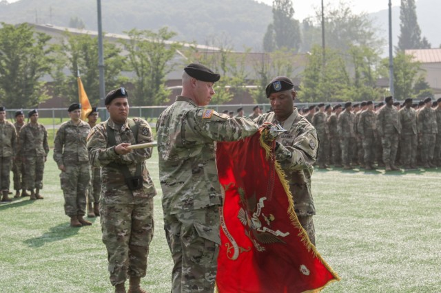 Lieutenant Col. James Raines (left), commander, 2nd Battalion, 18th Field Artillery Regiment (Rotational), 210th Field Artillery Brigade and Cartersville, Georgia native, and Command Sgt. Maj. James Platt Jr., 2-18 FAR command sergeant major and Tulsa, Oklahoma native, , unfurl the battalion colors during a transfer of authority ceremony, July 19, at Camp Casey, Republic of Korea. The 2-18 FAR is a multiple launch rocket system battalion assigned to 75th Field Artillery Brigade out of Fort Sill, Oklahoma and assumed its role as the rotational MLRS battalion after a seamless relief in place process with 3-13 FAR. (U.S. Army photo by Sgt. Osvaldo Martinez)