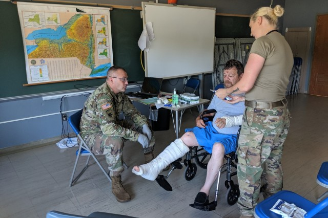 Maj. Richard Kalinowski and Spc. Sierra Chouinard are providing care for Charles Hoff, a Cortland County resident, during Healthy Cortland and Greater Chenango Cares Innovative Readiness Training mission held at Norwich Middle School in Norwich, New York on July 16, 2019.  The Joint IRT mission brought together servicemembers from the U.S. Air Force, Air National Guard, Air Force Reserve, U.S. Army, Army Reserve and U.S. Navy to provide medical support to the Cortland County community July 11-20, 2019. Photo by Maj. George Milevich, U.S. Army Reserve
