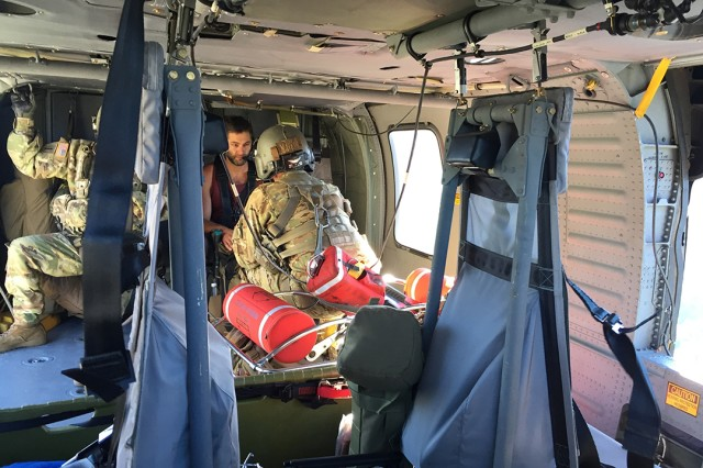 U.S. Army Staff Sgt. Greg Proell, a flight paramedic with the California Army National Guard's Army Aviation Support Facility #3 in Mather, California, talks with a hiker after a hoist rescue in Alpine County, Monday morning, July 22, 2019. The hiker was reported missing after failing to meet up with another hiker July 19 near Lake Alpine. The Cal Guard was activated Sunday night by the California Governor's Office of Emergency Services to assist Alpine County Sheriff's Department on the search.