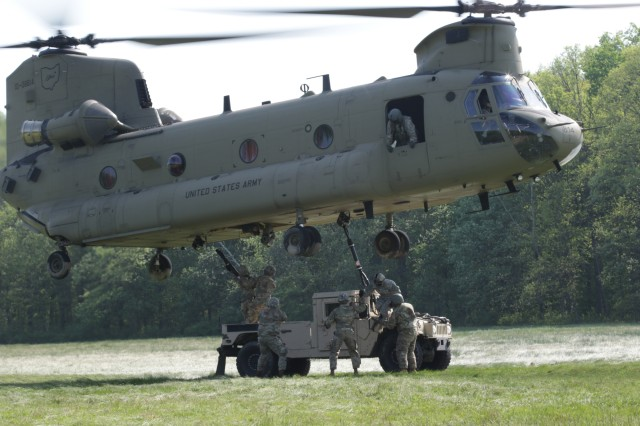 Ohio National Guard Soldiers link up a Humvee to the underside of a CH-47 Chinook helicopter during sling load operations training May 20, 2019, at Camp James A. Garfield Joint Military Training Center near Newton Falls, Ohio. Sling loads enables vehicles, equipment and supplies to be transported to remote areas inaccessible otherwise.