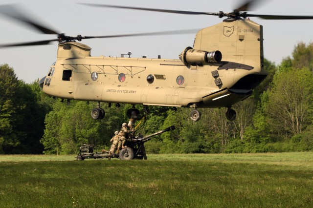 Ohio National Guard Soldiers attach an M777 howitzer to the underside of a CH-47 Chinook helicopter during sling load operations training May 20, 2019, at Camp James A. Garfield Joint Military Training Center near Newton Falls, Ohio. Sling loads enables vehicles, equipment and supplies to be transported to remote areas inaccessible otherwise.