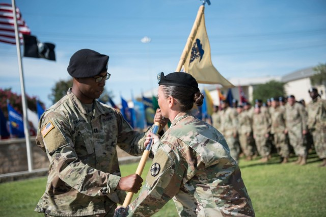 The 553rd Field Feeding Company Commander, Capt. Aramis M. Brewington, receives the guidon from 1st Sgt. Katrina M. Munoz, signifying the assumption-of-responsibility of the 553rd FCC July 23.  Before being activated July 23, 553rd established a name for themselves during the spring's Warfighter Exercise 19-4 providing meals for over 500 United States and coalition forces daily, providing support for 602nd Military Intelligence Battalion in Fort Huachuca, Arizona, during their field training exercise and providing support for III Corps and Fort Hood units. (U.S. Army photo by Sgt. 1st Class Kelvin Ringold)