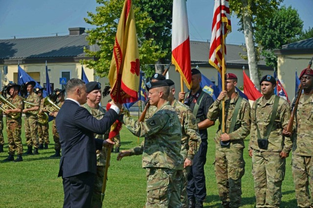 Tommy R. Mize, region director, Installation Management Command-Europe, receives the colors from Col. Erik M. Berdy, outgoing commander, during the garrison change of command ceremony on Hoekstra Field, Caserma Ederle, Vicenza, Italy, July 24, 2019.