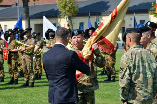 Col. Daniel J. Vogel assumes command of USAG Italy, as Tommy R. Mize, region director, Installation Management Command-Europe, passes the colors to him during the garrison change of command ceremony on Hoekstra Field, Caserma Ederle, Vicenza, Italy, July 24, 2019.