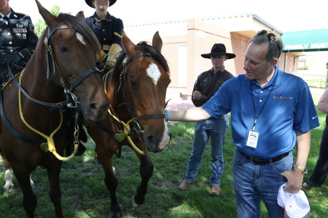 A Local leader meets the Fort Carson Mounted Color Guard as one of the several activities he and a diverse group of citizens engaged in during their visit to Fort Carson, July 18, 2019. The visit was part of a joint effort to help build connections between the Patriot Foundation and Fort Carson and to improve the local community's knowledge, support, and awareness of military life and operations. (U.S. Army Photo by Pfc. Matthew Rabahy)