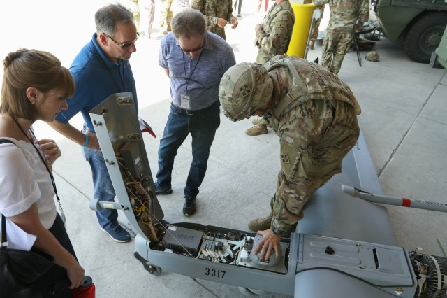 Local leaders watch a presentation on the RQ-7B Shadow given by a Soldier assigned to 299th Brigade Engineer Battalion, 1st Stryker Brigade Combat Team, 4th Infantry Division, while visiting Fort Carson, July 18, 2019. The visit was part of a joint effort to help build connections between the Patriot Foundation and Fort Carson and to improve the local community's knowledge, support, and awareness of military life and operations. (U.S. Army Photo by Pfc. Matthew Rabahy)