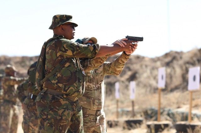 A Botswana Defense Force Commando holds a pistol while a North Carolina National Guard Special Forces Soldiers with B Company, 3rd Battalion, 20th Special Forces Group adjust his form on a firing range at Thebephatshwa Air Base in Botswana on July 13, 2019 after training on weapon holding techniques with. More than 170 Army and Air Guardsmen from North Carolina, Alabama and New Jersey training in partnership with their Botswanan Defense Force counterparts during Upward Minuteman 2019, a U.S. Africa Command exercise promoting the U.S. National Guard's State Partnership Programs on the African Continent.