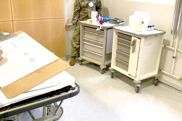 U.S. Army Sgt. Kie Young, the non-commissioned officer in charge of the Baumholder Behavioral Health Clinic, looks behind furniture in the clinic's Tracer Escape Room for deficiencies according to The Joint Commission standards.