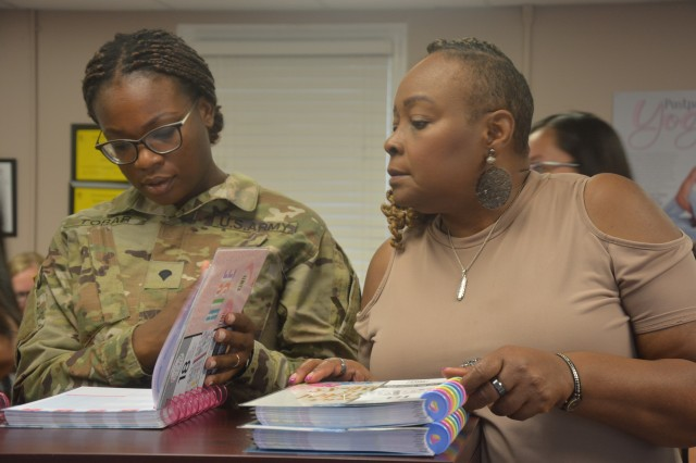 Spc. Kialonia Tobar, 116th Military Intelligence Brigade, and Marilyn Maze, a retired Army nurse, peruse planners before selecting one to make their own during a planner workshop held at the Family Outreach Center on July 18.