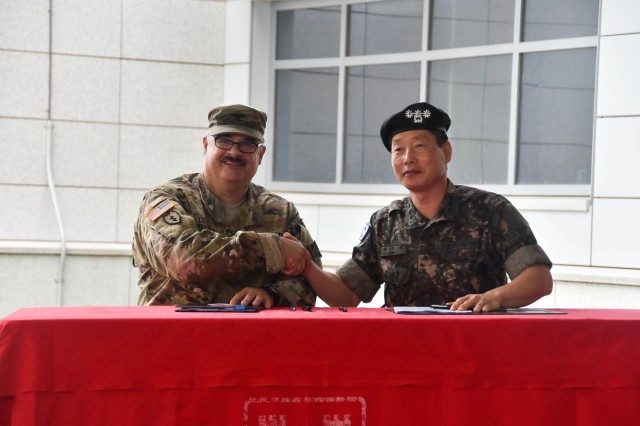 Col. Garrett Cottrell (left), Deputy Commanding Officer - Transformation, United States Army Corps of Engineers (USACE), Far East District (FED) and Col. Lee, Woo-Sig, Chief, Program Management Team, Ministry of National Defense U.S. Forces Korea Relocation Office (MURO), sign the Acceptance Release Letter for the new Brian D. Allgood Army Community Hospital at U.S. Army Garrison Humphreys, South Korea, July 24, 2019.