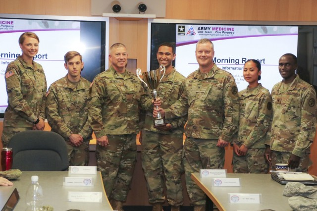 The Landstuhl Regional Medical Center Army ten-miler team presents Col. Michael Weber, commander, LRMC, and Command Sgt. Maj. Thurman Reynolds, command sergeant major, LRMC, with the team trophy from a recent Army ten-miler qualification race, July 12. The team consists of (from left) 1st Lts. Paige Runco, William McCray, Pfc. Ruben Ferreira, and Spcs. Fenny Descuatan and Mark Kogo. (U.S. Army photo by Gia Oney)
