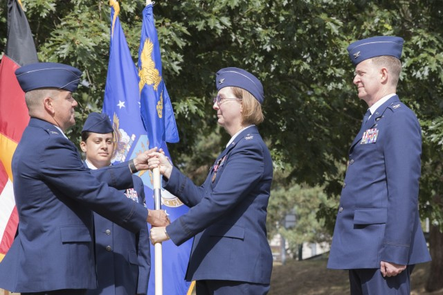 Air Force Col. Michael Roberts (left), commander, 86th Medical Group, receives the 86th Medical Squadron unit colors from Col. Regina Paden, outgoing commander, 86th MDS, during a change of command ceremony at Landstuhl Regional Medical Center, July 19.