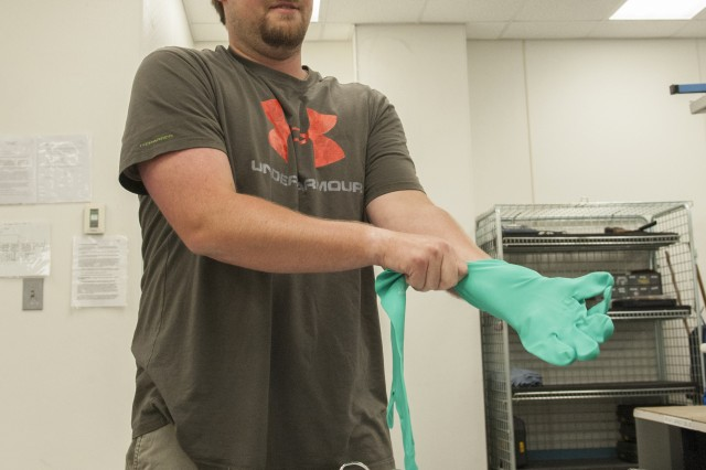 Isaac Gunn dons protective gloves, as required by safety data sheets, before opening a chemical for use in Anniston Army Depot's Electronics Branch.