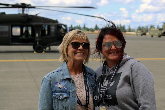 Melissa Boudreau, Career and Technical Education director (Right) and Denise Prescott, Administrative Assistant (Left) from Kelso High School pose with a Blackhawk helicopter at Grays Army Airfield, Joint Base Lewis-McChord, Wash. on June 24, 2019. The ride was part of an educator lift conducted by the Washington Army National Guard's Recruiting and Retention Battalion. The purpose of the event is to educate attendees on the Washington National Guard's benefits and programs.