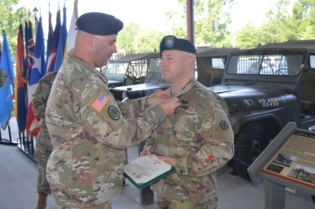 Outgoing 690th Rapid Port Opening Element Commander, Maj. Brett Dunning receives the Meritorious Service Medal for his service over the past two years at the Army's Transportation Museum at Fort Eustis, Virginia, July 26, 2019.