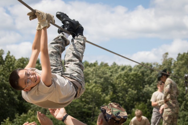 A cadet pulls himself across the overhead rope at station number 6, the One Rope Bridge, at the Teamwork Development Course July 23.