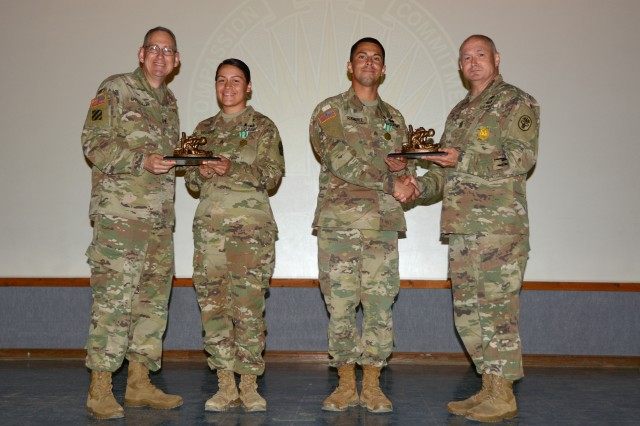 Brig. Gen. Ned Appenzeller, left, and Command Sgt. Maj. Joseph Cecil, right, hand trophies to Sgt. Samantha Delgado, center left, and Sgt. Kevin Ramirez, center right, at the Regional Health Command-Central Best Medic Ceremony on Camp Bullis. Delgado and Ramirez will represent Brooke Army Medical Center and Regional Health Command-Central at the Army Medicine Best Medic Competition in the fall.