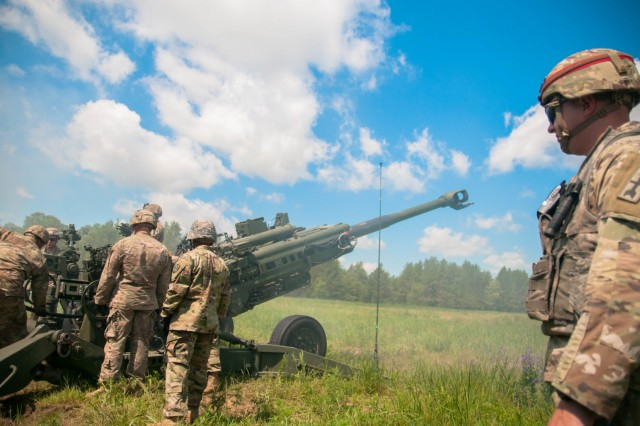 Ssg. Matthew Schoff (right), a cannon crewmember instructor at the Wisconsin National Guard's Regiment (Field Artillery) Regional Training Institute (RTI) observes a team working during their culminating live-fire exercise (LFX) at Ft. McCoy, Wis., July 27, 2019.