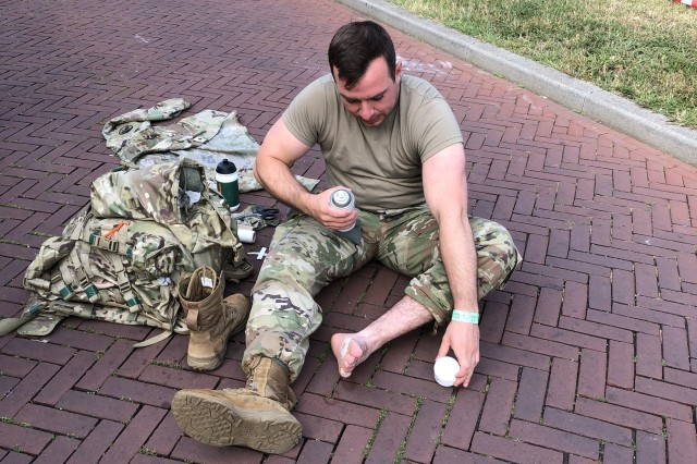 Spc. Robert Williamson, soldier with the U.S. Army Health Clinic Stuttgart and participant in the 103rd edition of the International Four Days Marches Nijmegen, takes a break to render self-aid to his feet. Nijmegen, or Vierdaagse in Dutch, is the largest marching event in the world that occurred for four consecutive days July 16-19, 2019. Over 450 U.S. service members were among the nearly 6,000 military marchers, and more than 40,000 civilians from around the world who marched 100 miles in four days in and around the Dutch city of Nijmegen. (Courtesy Photo)