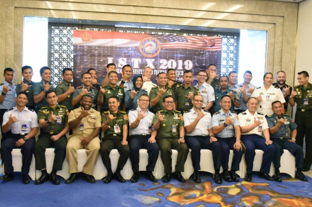 United States and Indonesia service members pose for pictures during the opening ceremony of the 2019 Information System and Technology Exchange, July 24, 2019, Jakarta, Indonesia. This year's third annual ISTX falls under the Hawaii National Guard's State Partnership Program, and aims to share best practices, assist in cyber security doctrine development, and enhance the cyber security capabilities to effectively defend and protect critical cyber information infrastructure from malicious virus and cyber intrusion. (U.S. Army National Guard Photo by Staff Sgt. Katie Gray)