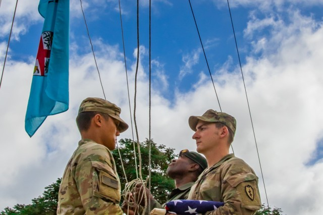 U.S. Army Sgt's. Darrin Clapham (left), and Devon Minardo, who serve with 1st Battalion, 27th Infantry Regiment, 25th Infantry Brigade Combat Team, open a U.S. flag in preparation to raise it, while Fijian Army Sgt. Ilaitia Ratubuli, who serves with 3rd Battalion Fiji Infantry Regiment, raises Fiji's flag in Labasa, Fiji, July 29. The flag raising ceremony was during the opening ceremony of Exercise Cartwheel 2019. The exercise will run two weeks from July 29 through August 12, and will provide tough and realistic training, strengthening Republic of Fiji Military Forces and US Army capacity as a regional leaders, increasing security cooperation for a free and open Indo-Pacific.