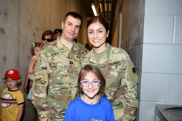 U.S. Army Reserve Capt. Michael Ariola, left, and Sgt. Maribel Meraz, assigned to the 85th U.S. Army Reserve Support Command headquarters, pause for a photo with Mae Gossage, 8, who wanted to meet Meraz and stated that she did not know that women can join the Army, during the American Association of Independent Professional Baseball's Chicago Dogs baseball home game, July 28, 2019, at Impact Field in Rosemont, Illinois against the Cleburne Railroaders. Soldiers from the 85th USARSC attended there for pre-game activities to conduct a ceremonial first pitch and a presentation of colors. Col. Daniel Jaquint, G3/Operations, was honored throwing in a first pitch and the 85th USARSC color guard team presented the Nation's colors during the playing of the National Anthem. Jaquint twice deployed across his three decades of service. Meraz, color guard non-commissioned officer-in-charge, has been mobilized for two deployments across her 11 years of service in the Army Reserve. The 85th U.S Army Reserve Support Command's nine Brigade Support Elements, and 45 Army Reserve battalions, dispersed across 25 states, provide observer coach/trainer support to assist First Army with mobilization certification for deploying Army Reserve and National Guard units. (U.S. Army Reserve photo by Anthony L. Taylor)