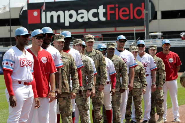 Army Reserve Soldiers assigned to the 85th U.S. Army Reserve Support Command headquarters pause for a photo with players from the American Association of Independent Professional Baseball's Chicago Dogs baseball team, July 28, 2019, at Impact Field in Rosemont, Illinois during a home game there against the Cleburne Railroaders. Soldiers from the 85th USARSC attended there for pre-game activities to conduct a ceremonial first pitch and a presentation of colors. Col. Daniel Jaquint, G3/Operations, was honored throwing in a first pitch and the 85th USARSC color guard team presented the Nation's colors during the playing of the National Anthem. Jaquint twice deployed across his three decades of service. Sgt. Maribel Meraz, color guard non-commissioned officer-in-charge, has been mobilized for two deployments across her 11 years of service in the Army Reserve. The 85th U.S Army Reserve Support Command's nine Brigade Support Elements, and 45 Army Reserve battalions, dispersed across 25 states, provide observer coach/trainer support to assist First Army with mobilization certification for deploying Army Reserve and National Guard units. (U.S. Army Reserve photo by Anthony L. Taylor)