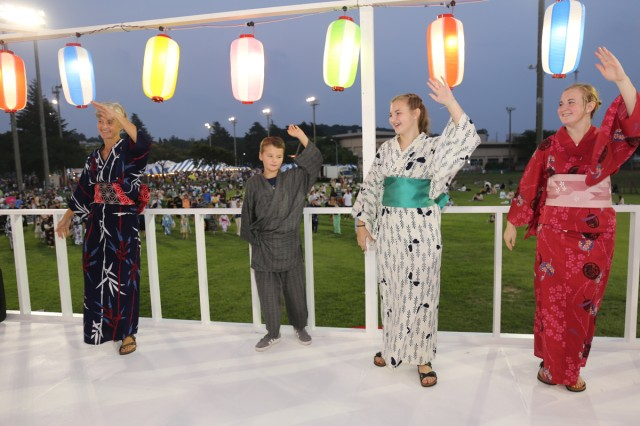 Several community members perform a traditional Japanese dance on the tower during the 59th annual Bon Odori Festival held Aug. 4, 2018, on Camp Zama, Japan. Since its inception in 1959, Camp Zama's Bon Odori Festival has been a way for the Army community in Japan to participate in and learn more about Japanese culture, and to share that experience with their host-nation neighbors. This year will mark the 60th anniversary of the Bon Odori Festival at Camp Zama.