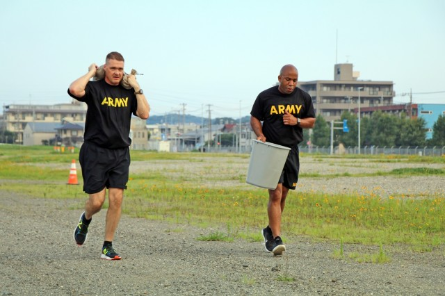 SAGAMIHARA, Japan - Command Sgt. Maj. Neil Sartain, a native of Memphis, Tennessee, 38th Air Defense Artillery Brigade senior enlisted advisor and Master Sgt. Leverion Wynn, Dudley, North Carolina native, logistician, 38th ADA Brigade, negotiate an obstacle as teammates during the Amazing Race at Sagami General Depot, July 30. Senior noncommissioned officers of units throughout Camp Zama participated in the Amazing Race as a team-building exercise to inspire esprit de corps and challenge themselves, both physically and mentally.