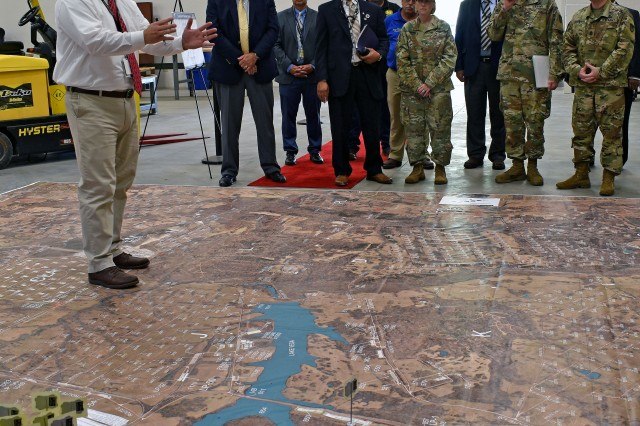Commanding General of the Joint Munitions Command Brig. Gen. Michelle M.T. Letcher (C) receives a briefing from Depot Plans and Operations Specialist Matt Smith (L) on the installation's consolidated outloading process with the help of a large scale map. To the left of Letcher is Depot Commander COL Joseph Kurz and JMC Command Sergeant Major Brian Morrison. Letcher was visiting the Depot as part of her quarterly review of installations under her command.