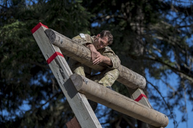 An Air Force Tactical Air Control Party Airman assigned to the 5th Air Support Operations Squadron, Joint Base Lewis-McChord climbs on top of an obstacle during the 2019 Lightning Challenge at JBLM July 29.
