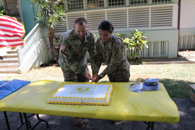 Lt. Col. Michael Friess, the 8th Theater Sustainment Command Staff Judge Advocate and Spc. Samantha Marfisi, paralegal specialist assigned to the 130th Engineer Brigade and the youngest JAG Corps Soldier in attendance participate in a cake cutting during the ribbon cutting ceremony, July 29 celebrating the 8th TSC Staff Judge Advocate Office move to Building T123 on historic Palm Circle and the 244th Birthday of the Army JAG Corps.
