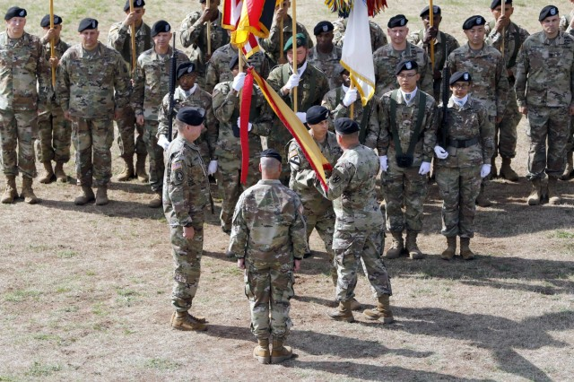 Command Sgt. Maj. Rocky Carr, 21st Theater Sustainment Command senior enlisted advisor, passes the 21st TSC colors to Maj. Gen. Steven Shapiro during the 21st TSC change of command ceremony July 31, 2019 on Daenner Kaserne in Kaiserslautern, Germany. The passing of the colors signifies the last act of allegiance to Shapiro as the commander. (U.S. Army photo by Sgt. Benjamin Northcutt, 21st Theater Sustainment Command.)