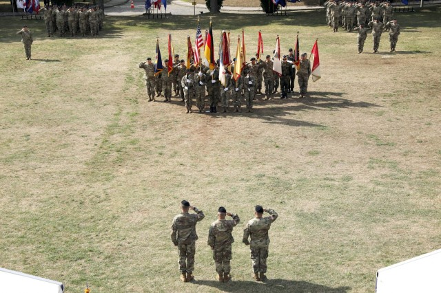 Lt. Gen. Christopher Cavoli (bottom center), commanding general U.S. Army Europe, Maj. Gen. Christopher Mohan (bottom left), incoming commanding general 21st Theater Sustainment Command, Maj. Gen. Steven A. Shapiro (bottom right), outgoing commanding general of 21st TSC, render honors during the 21st TSC change of command ceremony July 31, 2019  on Daenner Kaserne in Kaiserslautern, Germany. The massing of the colors includes all the brigades within 21st TSC and the 21st TSC color guard. (U.S. Army photo by Sgt. Benjamin Northcutt, 21st Theater Sustainment Command.)