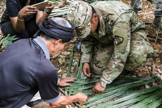 Cpt. Hj. Sofian Bin Harun, retired, left, shows Cadet Cassidy Braggs, USMA Class of 2021, right, how to build a shelter cover from the leaves of a tree during jungle survival skills training. Cadets and midshipmen from the U.S. Military Academy at West Point, U.S. Air Force Academy, and U.S. Naval Academy learn jungle survival skills at Kongkoi Camp, Jelebu, Negeri Sembilan, Malaysia July 24, 2019. This is the first time in history all three academies have participated in the leadership exchange at the same time. (U.S. Army photo by Sgt. 1st Class Josephine Pride)