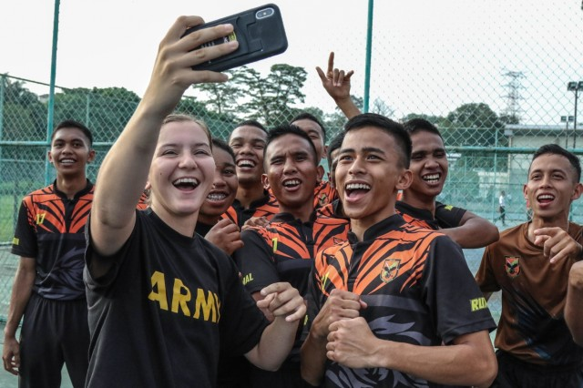 Cadets Stephanie Dudgeon and Cassidy Braggs, USMA Class of 2021, take a selfie with a group of Malaysian cadets at the National Defense University-Malaysia after a game of volleyball July 21, 2019. Cadets and midshipmen from the U.S. Military Academy, U.S. Air Force Academy, and U.S. Naval Academy came together for a student leadership exchange at the NDUM from July 20-28. This is the first time in history all three academies have participated in the exchange at the same time. (U.S. Army photo by Sgt. 1st Class Josephine Pride)