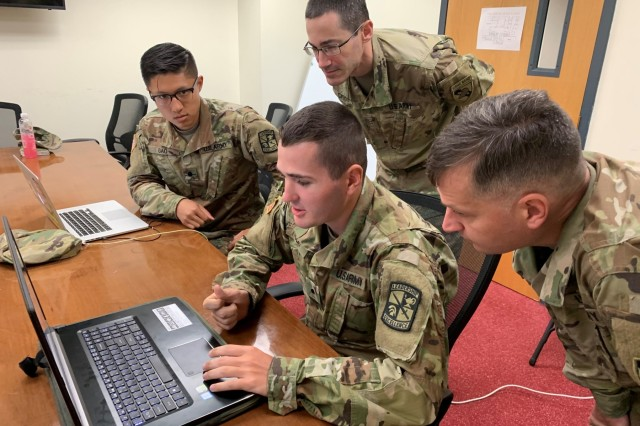 CW2 Jonathan Crane, USMA Band, and Lt. Col. Stephen Hamilton, Army Cyber Institute and USMA faculty, observe the data analysis on social media text sentiment that ROTC Cadet Darien Cupit, Colorado State University, and ROTC Cadet Daniel Gao, Northeastern University, researched during their ACI Summer Internship Program at West Point.