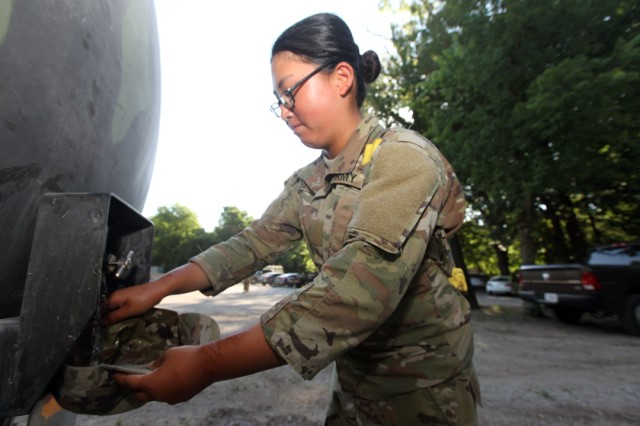 Knowing that cool heads prevail during basic combat training, Pvt. Miseon Yu, D/1-31st FA, fills her patrol cap with water from a water buffalo July 18, 2019 at the 1st Lt. Frederick Henry Medical Training Lanes. She had already uncuffed her sleeves to get a better airflow through her uniform.