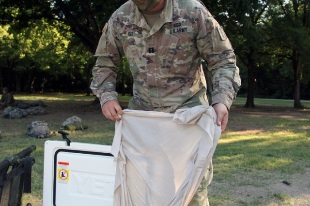 Capt. Dylan Rice, D/1-31st FA commander, demonstrates how iced sheets are used to treat BCT trainees suffering from heat injuries July 18,2019, at the 1st Lt. Frederick Henry Medical Training Lanes. With the current high temperatures the iced sheets are getting much use by units training in the field.