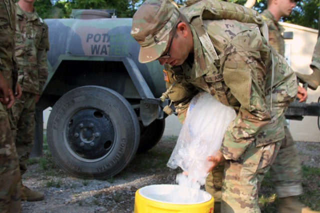 Trainees pour ice into 5-gallon jugs of water July 18, 2019, at Fort Sill. The jugs will be strategically placed around a training site for easy access by trainees to hydrate themselves.
