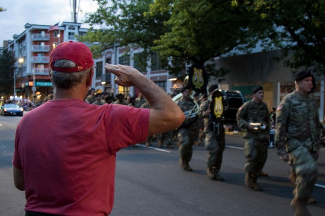 A spectator salutes Soldiers with America's First Corps Army Band in the Seafair Alaska Airlines Torchlight Parade in Seattle, July 27, 2019. Celebrating its 70th anniversary, Seafair is a 10-week long festival focused on building community and celebrating Seattle's diverse cultural landscape. The Soldiers' presence at the parade serves to highlight the importance of maintaining relationships with surrounding communities through events like these. (U.S. Army photo by Spc. John Weaver)