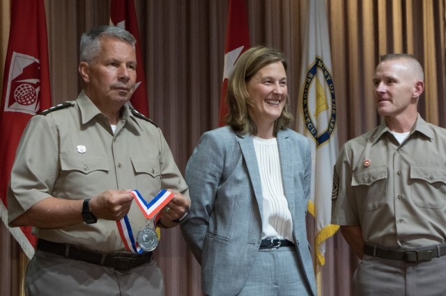 Tambour Eller, deputy district engineer for programs and project management at Sacramento District, U.S. Army Corps of Engineers, smiles Aug. 1, 2019, as Lt. Gen. Todd Semonite, USACE Commanding General, prepares to present her with the USACE Civilian of the Year Award as Command Sergeant Major Brad Houston looks on.