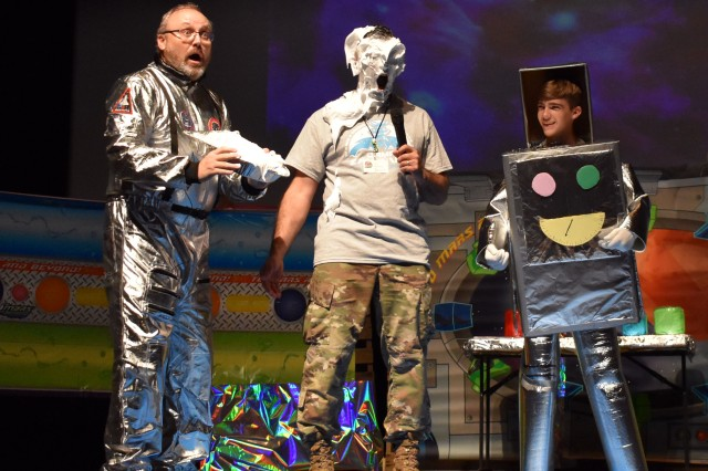 Col. Thomas Matelski, center, commander, U.S. Army Garrison Japan, reacts after Scott Yeager, left, director of religious education, USAG Japan, gave him a shaving-cream pie in the face during the closing ceremony of Vacation Bible School at Camp Zama, Japan, Aug. 2. Justin Greene, 14, a volunteer, looks on.