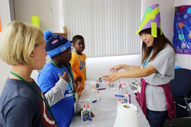 Kiyoko Yokoya , a volunteer, introduces children to a science activity during Vacation Bible School at Camp Zama, Japan, July 31.